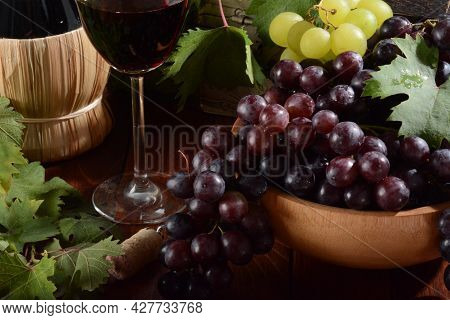 Fresh Black Grapes In Wooden Bowl On Wooden Table With Red Wine
