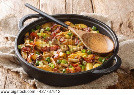 Freshly Fried Potato Wedges With Green Onions, Mushrooms And Bacon Close-up In A Frying Pan On A Woo