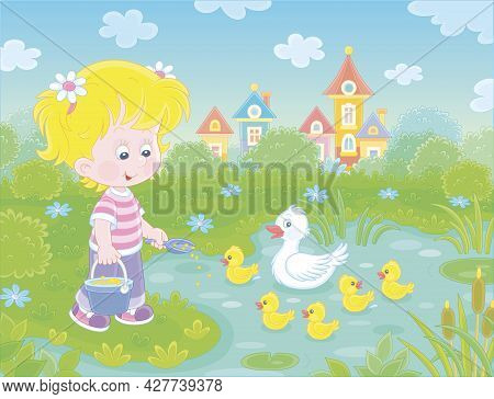Little Girl Farmer Standing With A Bucket Of Feed Grain And Feeding A Merry Brood Of Small Yellow Du