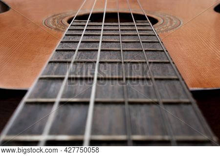 Close-up Of Old Acoustic Guitar Fretboard With Selective Focus In The Center. Neck Perspective With