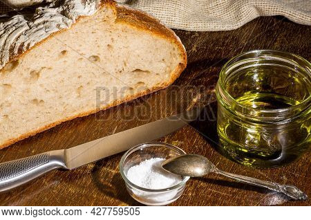 Still Life - Yeast-free Buckwheat Bread With Olive Oil And Coarse Salt In Glass Jars, A Knife, And A