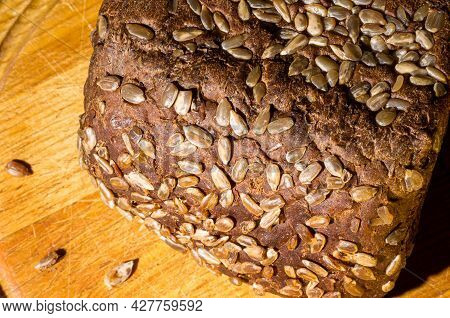 Still Life - Black Bread With Sunflower Seeds, And A Linen Napkin On A Wooden Board, Wooden Backgrou