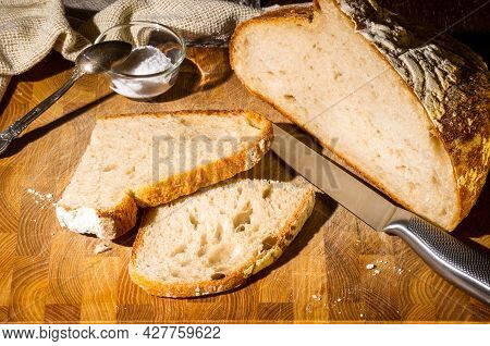 Still Life - Yeast-free Buckwheat Bread With Sliced Pieces, And Coarse Salt In A Glass Jar, A Knife,
