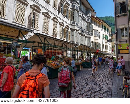 Bolzano, Italy, June 2021. At The Local Market, People Walk Among The Stalls Looking At The Goods. B