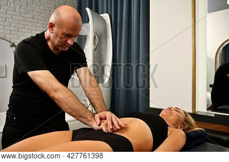 A Professional Massage Therapist In Wellness Spa Center Gives An Anti-cellulite Massage To A Woman L