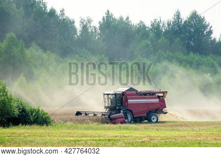 Combine Harvester Harvest Wheat Crop In The Clouds Of Dust