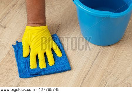 Gloved Hand Washes A Laminate Flooring With A Wet Cloth