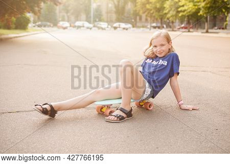 Adorable Young Girl Smiling To The Camera, Sitting On Her Pennyboard In The City