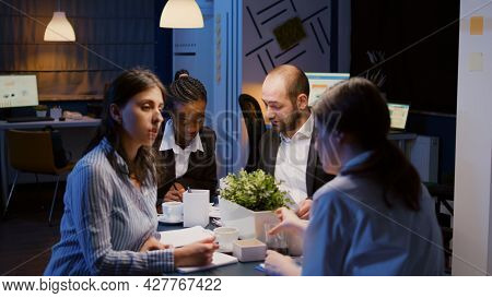 Multi Ethnic Entrepreneurs Sitting At Conference Table Overworking At Company Solution Presentation