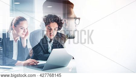 Group Of Business People In Formal Suits Working Together On Laptop, Pensively Looking Into A Displa