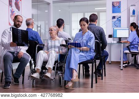 Doctor Holding Patient X-ray Explaining Diagnosis To Nurse And Disabled Woman In Waiting Area. Paral