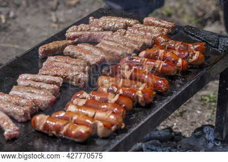 Grilling Meat On Bbq Stone Grill In Nature. Preparing Cevapi And Kobasice Or Kebab And Sausages For