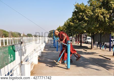 Burmese Monk Old Men Playing Exercise On Equipment Playground Beside Road Of Water Moat Canal Of Man