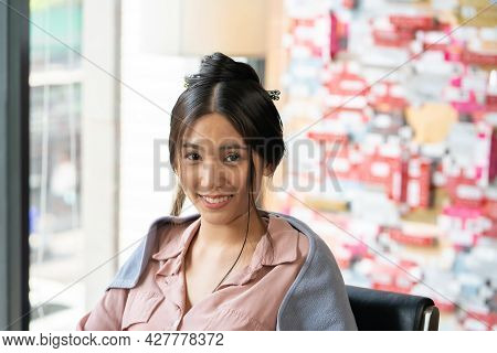 Young Pretty Asian Women Sitting Inside Hair Salon, Smiling While Choose New Hair Dye Color And Hair
