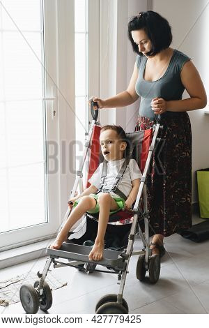 Mother With Disabled Child In Big Stroller. Accessibility Of People In Wheelchairs And Prams. Woman