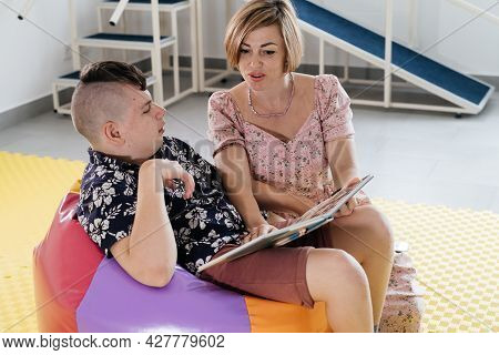 Children With Disability Reading Book And Communicating. Cerebral Palsy Boy Talking With Woman Tale