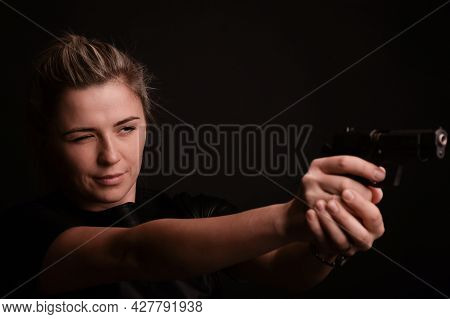 The Girl Narrowing Her Eyes, Aims To The Side From The Pistol, Which She Holds With Both Hands. The