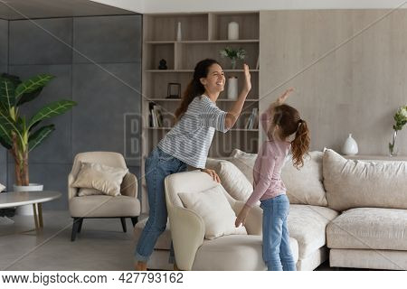 Smiling Hispanic Mom And Daughter Give High Five Five