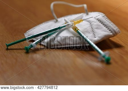 Syringe With Needle And Respirator. Concept For Health And Vaccination Against Covid 19 - Sars Cov 2