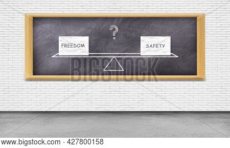 Freedom Concept : Freedom And Safety Text Wording Balancing On Seesaw Or Balance Scales On Chalkboar