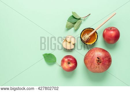 Rosh Hashanah. Apples, Pomegranate And Honey On A Green Pastel Paper Background. Jewish New Year. Tr