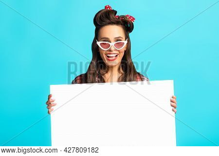 Shocked Pinup Woman In Retro Wear Presenting Something On White Blank Poster Over Blue Studio Backgr
