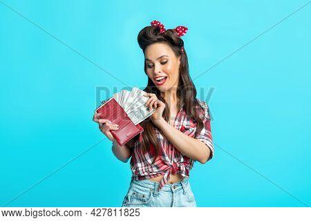 Joyful Pinup Lady In Retro Wear Taking Money From Full Wallet On Blue Studio Background. Wealth, Inc