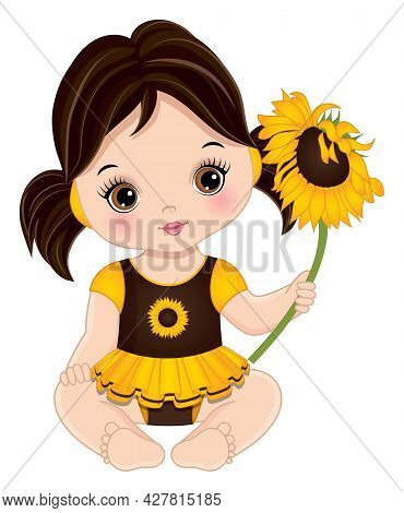 Cute Little Baby Girl Is In Yellow And Brown Dress Sitting. Dark-haired Little Girl Is With Ponytail