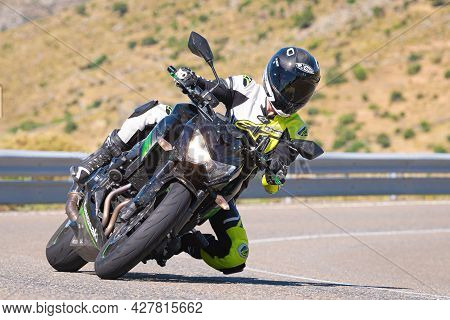 Biker Driving On The Road And Taking A Sharp Curve..