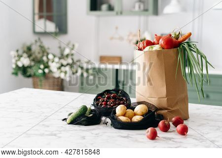Various Fresh Vegetables In Paper Grocery And Black Mesh Bags On Kitchen Island With Marble Top, Hea