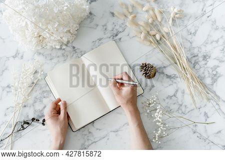 Cropped Shot Of Woman Writing In Blank Checkered Note Book With Pen, Table With Decorated White Marb