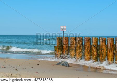 Wooden Breakwaters On The Seashore. Inscription In Russian: Located On The Breakwater Prohibited