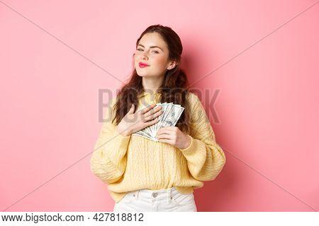 Smiling Girl Looks Satisfied And Grateful, Hugging Dollar Bills, Holding Money And Making Smug Face