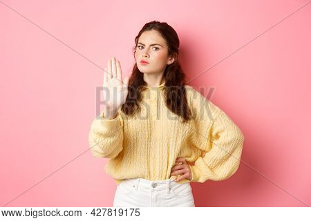 Angry And Bossy Young Woman Frowning, Looking Serious, Showing Block Stop Gesture, Stretch Out Hand