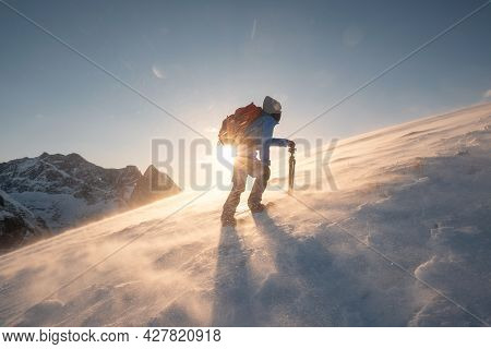 Man Photographer With Tripod Are Climbing On Slope Hill On Ryten Mount In Blizzard At Sunset