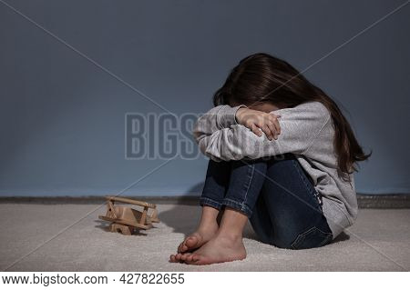 Lonely Sad Girl At Home. Saddened Alarmed Child Alone At Home.