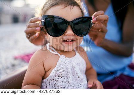Mom Puts Big Sunglasses On An Enthusiastic Little Girl