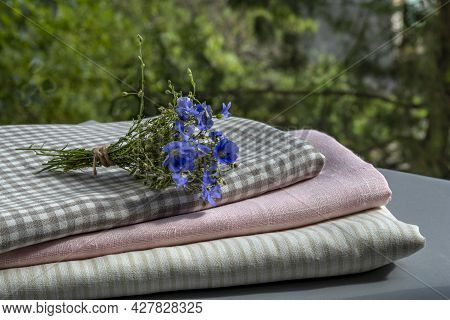 Bouquet Of Blooming Flax Lies On Stack Of Linen Home Textiles In Garden. Lat. - Linum Usitatissimum.