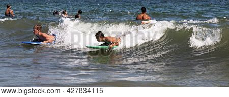 Babylon, New York, Usa - 24 July 2021: Two Boys Are Riding A Wave In The Atlantic Ocean On Boogie Bo