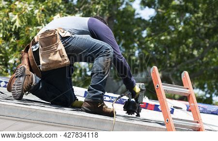 A Contractor Is Kneeling On A Residential Roof Using A Nailgun To Put New Roof Shingles On A House N