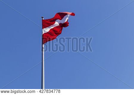 Red White Red Latvian National Flag On A Blue Sky Background.