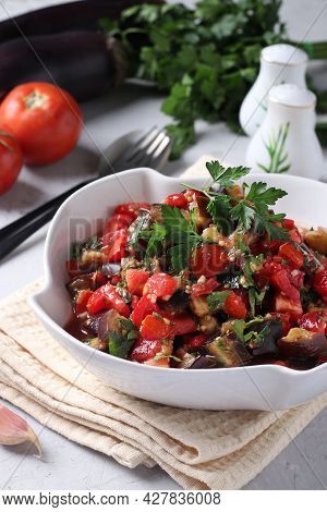 Salad With Eggplants, Tomatoes, Garlic And Parsley In A White Bowl On A Light Gray Background. Close