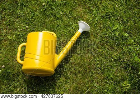 Yellow Watering Can In The Grass. Watering Can On The Garden.