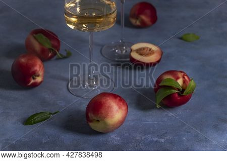 Several Ripe Peaches Or Nectarines And A Glass Of White Peach Wine Sit On A Blue Plaster-textured Su