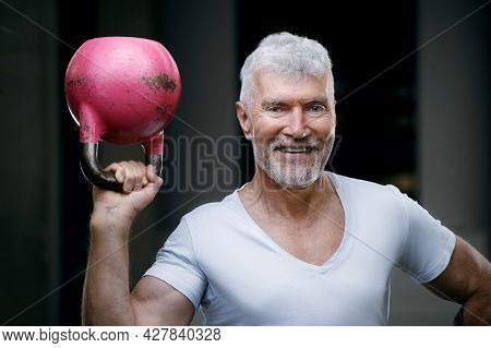 Handsome Gray Haired Senior Man With Kettlebell Weight In His Hand. Sport And Health Care Concept