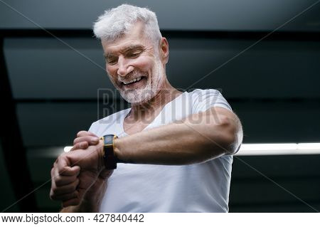 Handsome Gray Haired Senior Man Looking At Sport Watch In His Hand. Sport And Health Care Concept