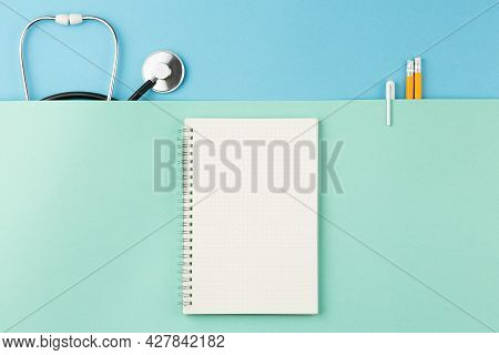 Open Spiral Notebook With Pen And Pencils On Top View Two Tone Background. Medical Stethoscope On Th