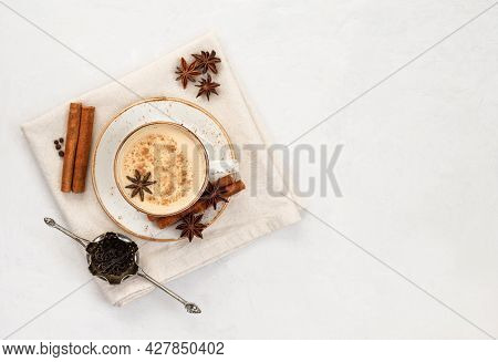 Masala Chai Tea. Traditional Indian Drink. Masala In A White Cup With A Napkin On A White Concrete B