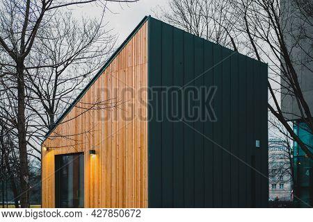Triangular House With Wooden And Black Facade With Light Illumination. Modern. Illuminated. Modular