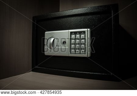 Small Modern Safe On Shelf In Dark. Small Safe Box Close Up In Low Key Light. Selective Focus